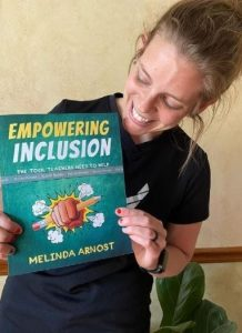"""Teacher and author Melinda Arnost smiles as she shows a copy of her book, """"Empowering Inclusion""""."""